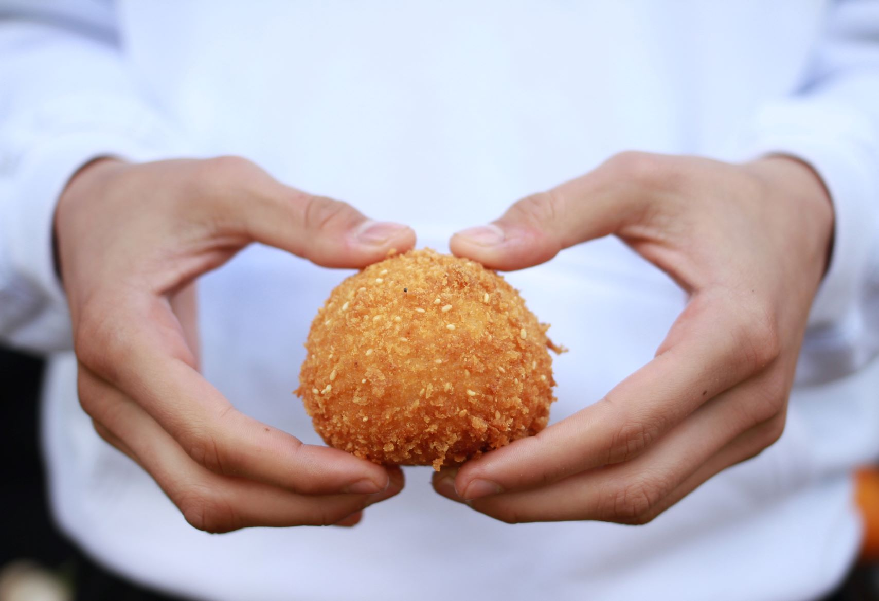 man about to break arancini ball in half using his hands, he is wearing and chefs coat