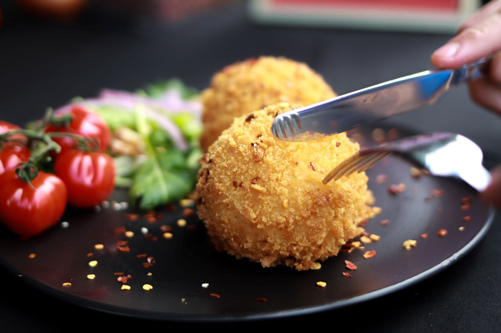 knife and fork about to cut into an arancini ball