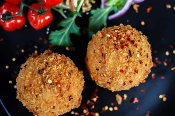 arancini with chilli flakes on top and small peppers and salad in the background