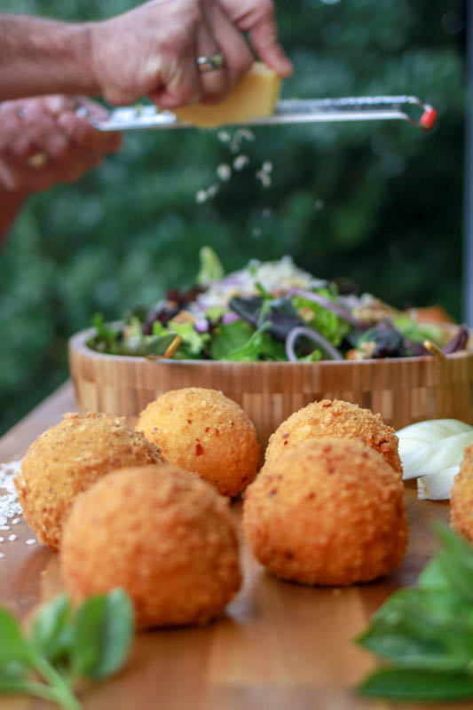 Arancini being held in someone's fingers